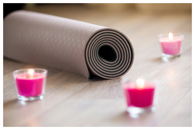 Rose-colored lighted pink wax candle and rolled brown yoga, pilates mat on the floor ready for workout. Close up. Healthy life, keep fit concepts. Focus on mat